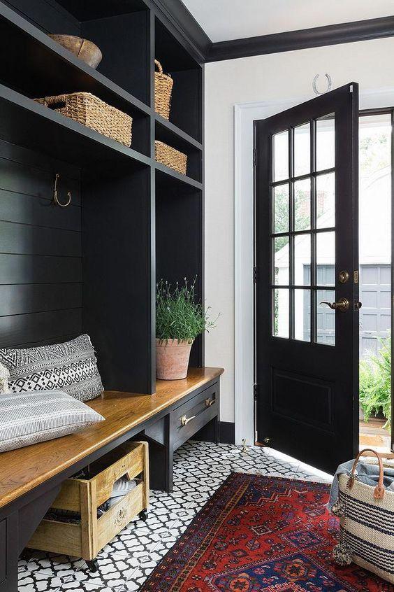 un piccolo ingresso di una fattoria con mobili color onice e una porta che contrasta con i tocchi bianchi e rossi dappertutto