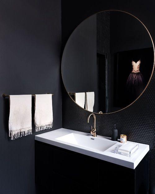 una toilette in onice con un lavandino bianco a contrasto, asciugamani bianchi e piastrelle nere lucide