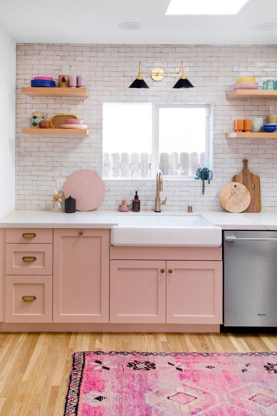 una piccola cucina fatta con armadi rosa, un tappeto stampato luminoso e neutri per creare un contrasto