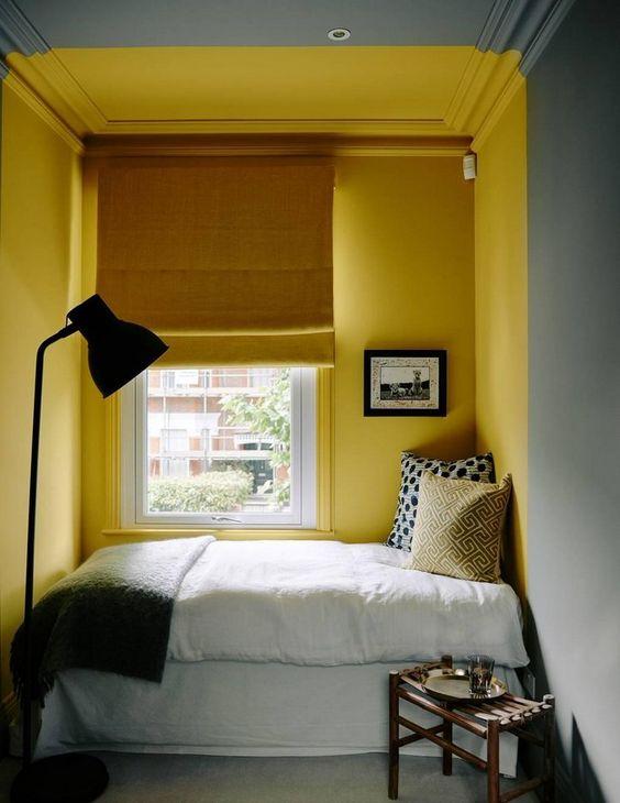un piccolo angolo di lettura con pareti giallo brillante che definiscono questo angolo nello spazio grigio