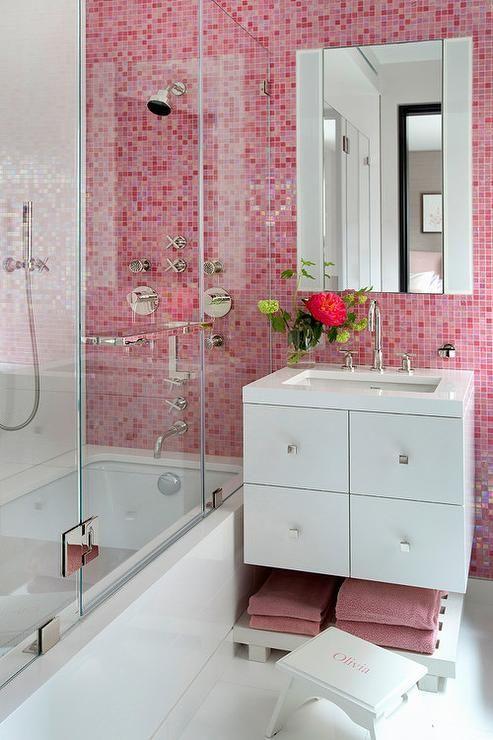 un bagno piccolo ma contrastante fatto in rosa e bianco, con un muro appariscente e asciugamani coordinati