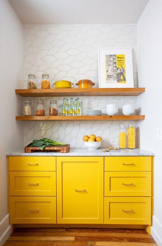 una minuscola cucina con armadi giallo brillante, tutti bianchi e ripiani in legno sopra gli armadietti