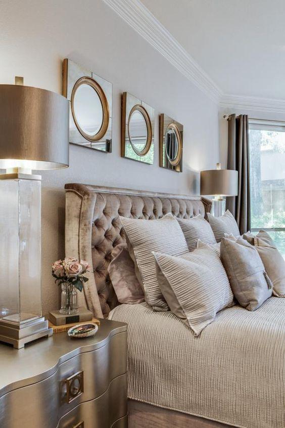 una camera da letto principale di transizione con un assortimento di oggetti metallici, specchi, una lampada, un comodino