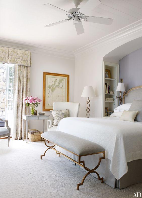 una camera da letto vintage realizzata in tutti i neutri, con una panca chic su gambe in ottone e una lampada da terra coordinata nell'angolo