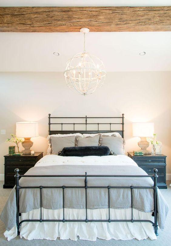una camera da letto di una fattoria con una trave di legno sul soffitto e un lampadario a sfera di tendenza appeso sopra