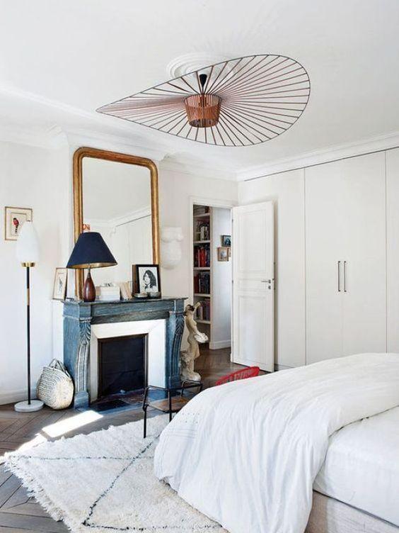 una romantica camera da letto parigina con un lampadario in rame di forma geometrica è wow