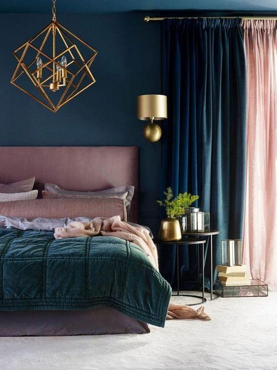 una camera da letto audace realizzata in verde acqua, verde scuro e rosa, con una fioriera d'oro, un'applique e un lampadario di tendenza