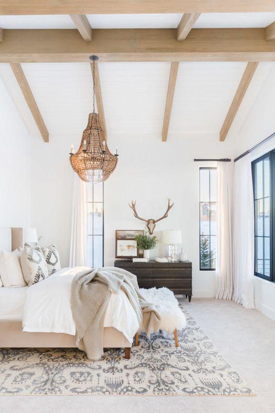 una camera da letto eclettica neutra con travi in legno sul soffitto, un lampadario in ottone con candele