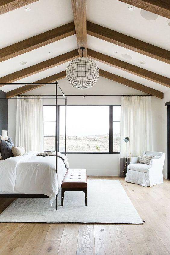una camera da letto neutra della fattoria con travi in legno sul soffitto e una lampada a sfera d'effetto