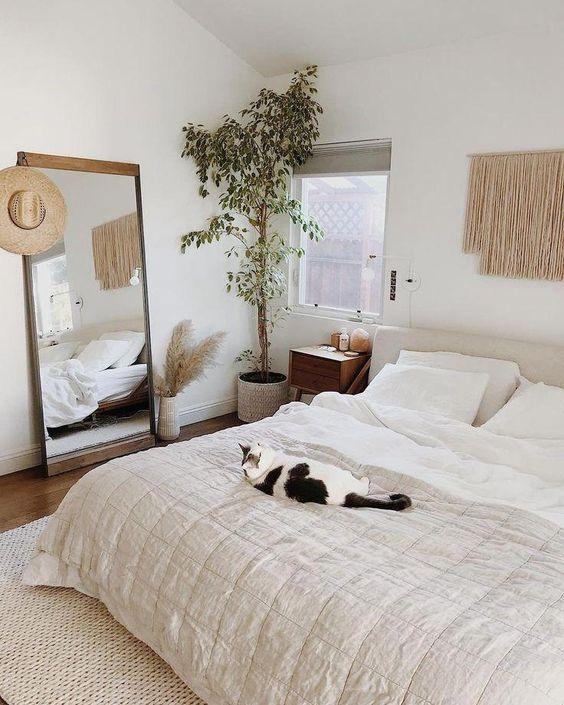 una camera da letto boho neutra con un'affascinante pianta in vaso nell'angolo che la rende più fresca e accogliente