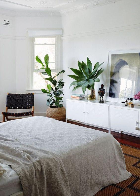 una camera da letto boho con due piante importanti che catturano l'attenzione e rinfrescano lo spazio
