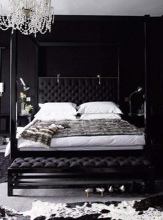 una camera da letto nera con un raffinato lampadario di cristallo che illumina lo spazio facendolo stupire