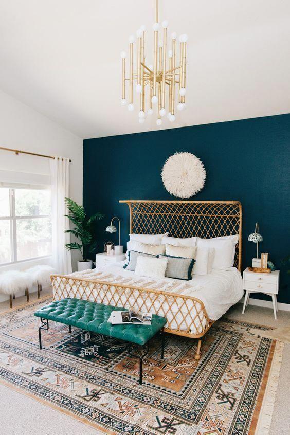 una camera da letto chic arricchita con una pianta in vaso, un lampadario d'oro e una disposizione di plaid