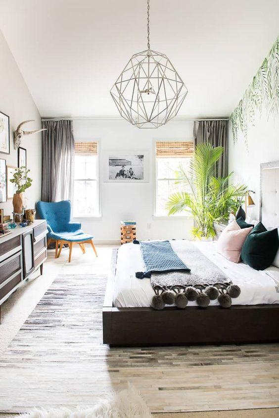 una camera da letto boho con una pianta tropicale dichiarata nell'angolo che attira l'attenzione