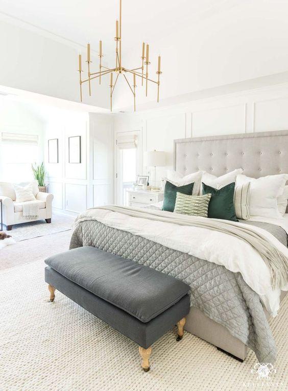 una camera da letto neutra con un letto formale grigio, una disposizione di cuscini