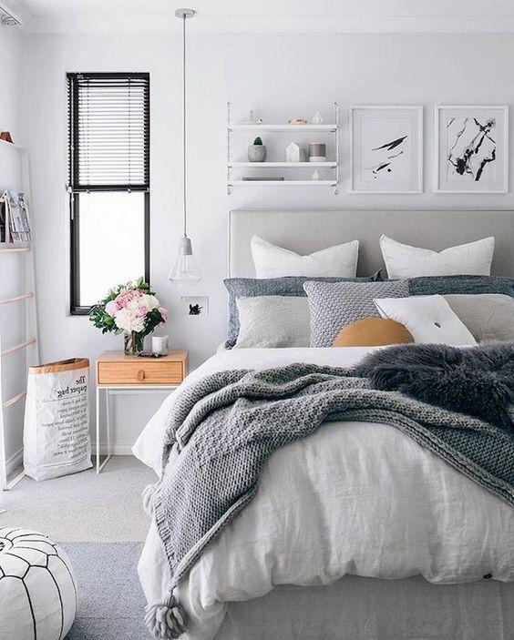 una camera da letto contemporanea con un arrnagement di plaid sul letto e coperte materiche