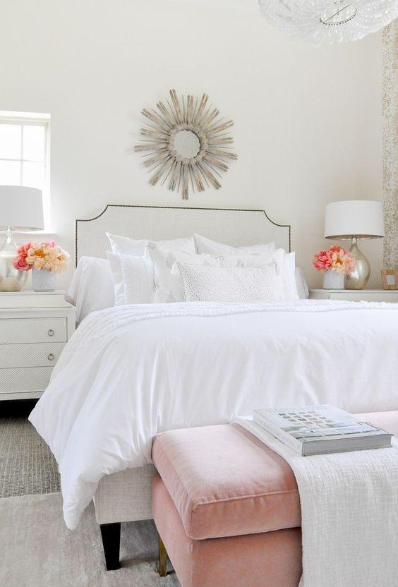 una camera da letto elegante e ariosa con un letto bianco e una disposizione di cuscini bianchi ma di vari tessuti
