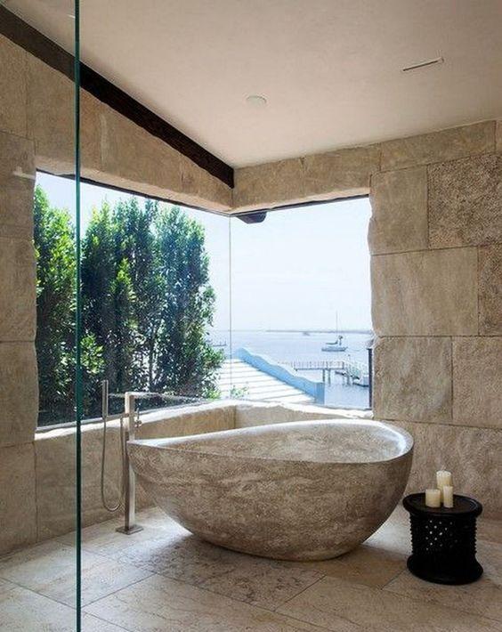 un bagno accattivante con vista sul mare, muri in pietra, piastrelle in pietra sul pavimento e una vasca da bagno in pietra accattivante