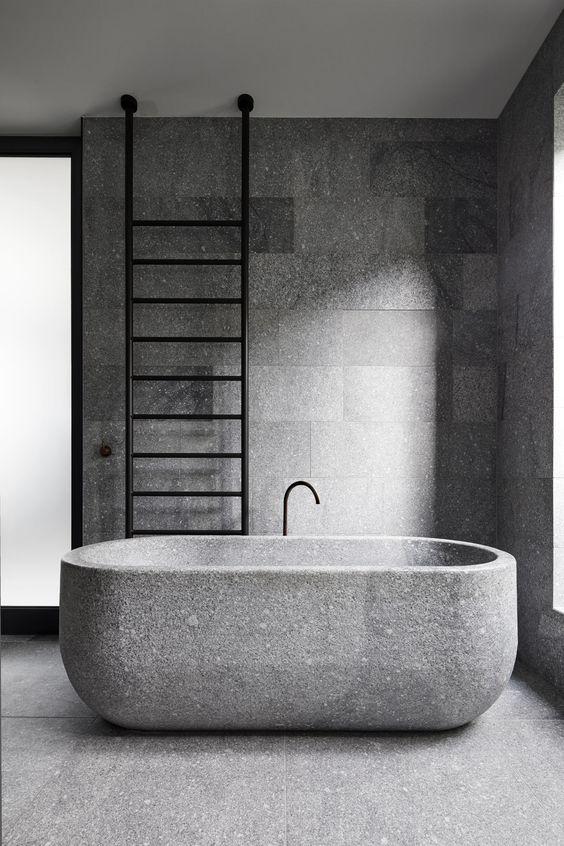 un bagno minimalista in granito con una vasca da bagno in granito e una scala nera è un'idea interessante per un'atmosfera spigolosa