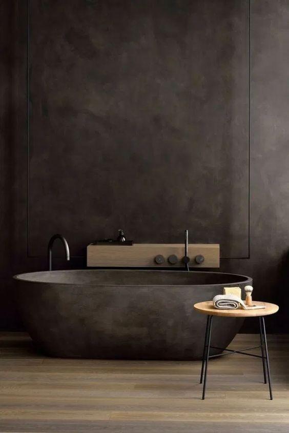 un bagno scuro e lunatico con una vasca da bagno in pietra nera, un mini tavolino e una mensola in legno sul muro