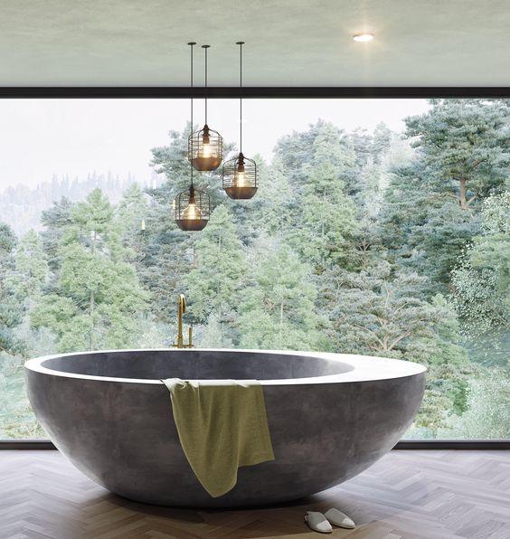 un bagno contemporaneo con una parete vetrata per una vista, una vasca da bagno in pietra arrotondata, lampade accattivanti per accentuare lo spazio