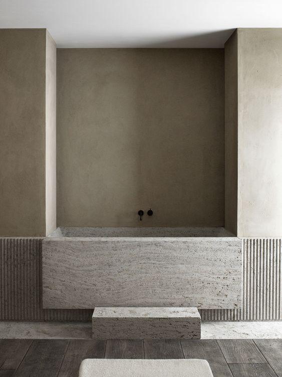 un bagno minimalista fatto in neutri, con una vasca da bagno in pietra incorporata e pavimento in legno scuro