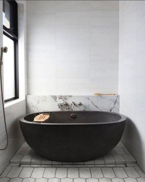 un bagno monocromatico contemporaneo con un muro in pietra blakc, piastrelle in marmo e geometriche e infissi scuri per un look audace