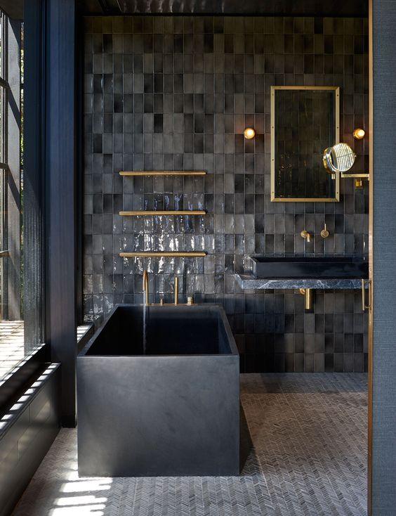 un bagno scuro con piastrelle del bagno, una vasca da bagno quadrata in pietra nera, un lavabo scuro, un lavandino nero e tocchi d'oro qua e là