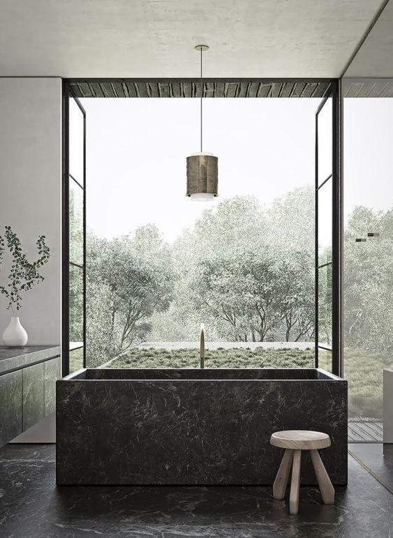 uno splendido bagno lunatico con una vasca da bagno in pietra quadrata nera e pavimenti coordinati e una vanità più una vista sul giardino