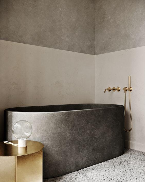 un bagno raffinato e minimalista con pareti color block, una vasca da bagno in pietra e un tavolino e accessori in oro lucido