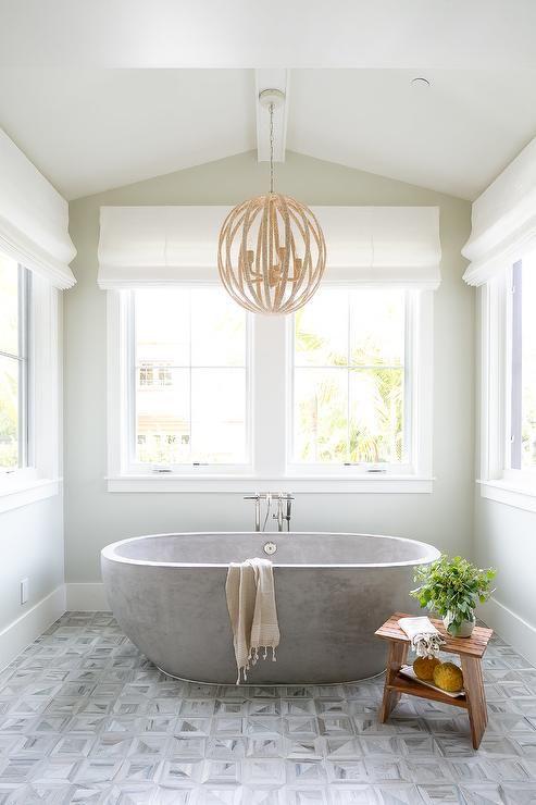un bagno da fattoria neutro con piastrelle stampate, una vasca da bagno in pietra neutra e un lampadario rotondo sembra sereno