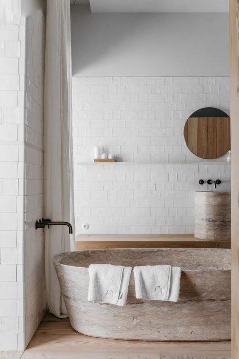 un bagno neutro con una splendida vasca in pietra e un lavandino abbinato sembra raffinato e molto naturale