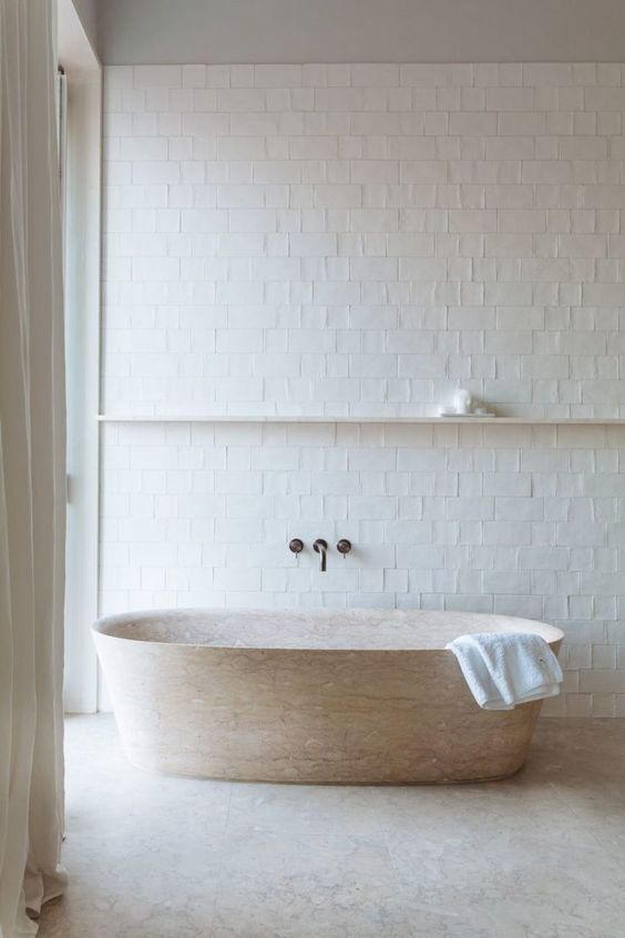 un bagno neutro con piastrelle bianche, una vasca da bagno in pietra e una mensola sospesa per una sensazione ariosa e serena nello spazio