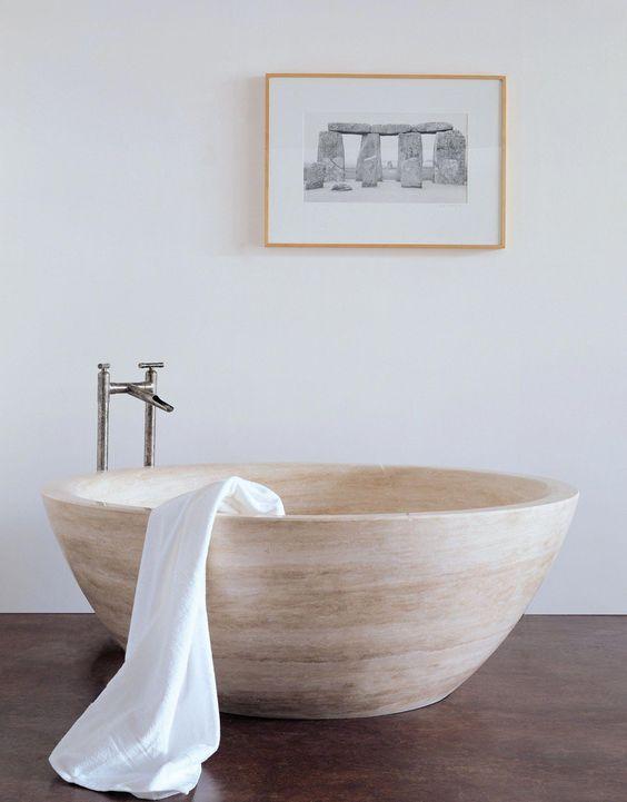 un bagno contemporaneo neutro con una vasca da bagno in pietra simile a una ciotola e un'opera d'arte accattivante per un tocco moderno