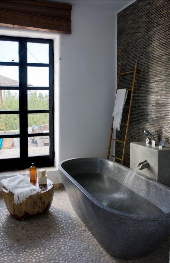 un bagno lunatico con una piastrella di ciottoli bianchi, pietra scura sul muro e una vasca da bagno in pietra scura più un tavolino in legno