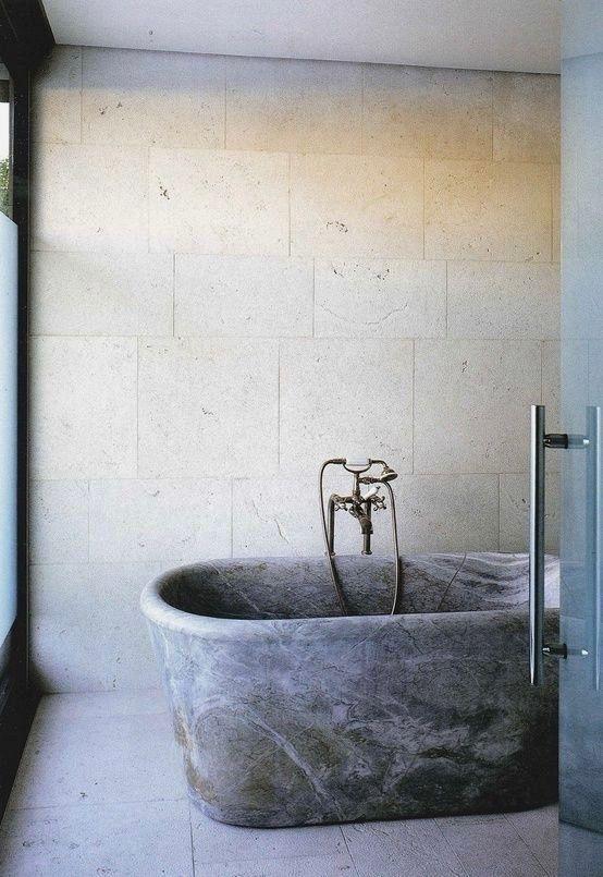 un bagno neutro con piastrelle materiche sulle pareti e sul pavimento, una vasca da bagno in pietra grigia e infissi in metallo scuro