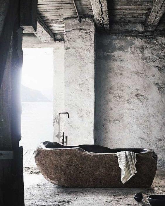 un bagno grezzo con una vasca in pietra scolpita che risalta e fa una dichiarazione di moda insieme a una vista sul mare