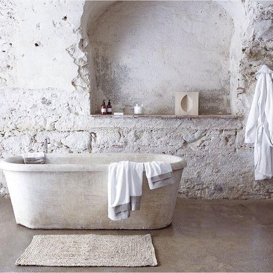 un bagno bianco con piastrelle in pietra grezza, una vasca da bagno in pietra bianca e un tappeto di iuta è tutto naturale e rilassante