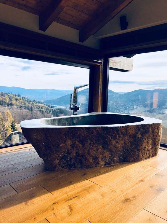 un bagno rustico con una vista fantastica, pavimenti in legno e una vasca da bagno in pietra scura scolpita da un unico pezzo di pietra