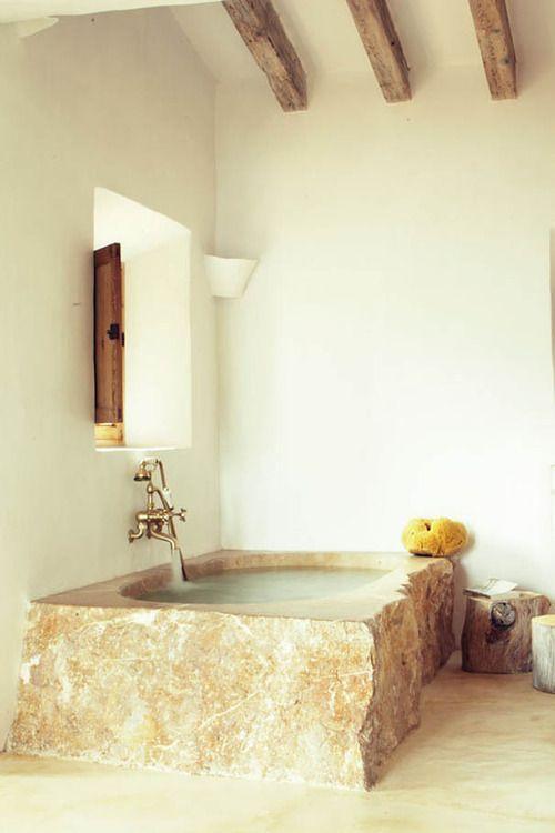 un bagno rustico con pareti bianche, travi in legno, una vasca da bagno in pietra grezza in una tonalità calda e tronchi d'albero come tavolini