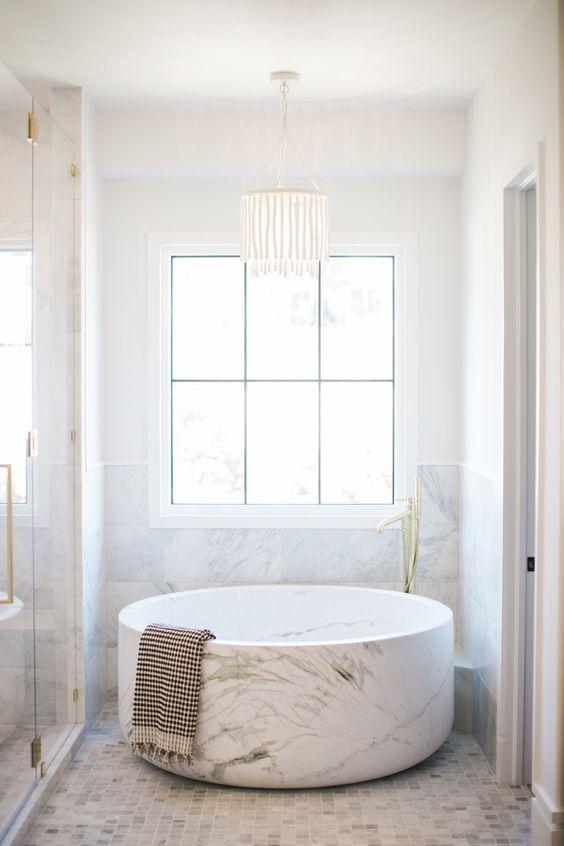un piccolo ma raffinato bagno neutro rivestito con piastrelle di marmo, con una mezza parete in marmo e una vasca rotonda in marmo