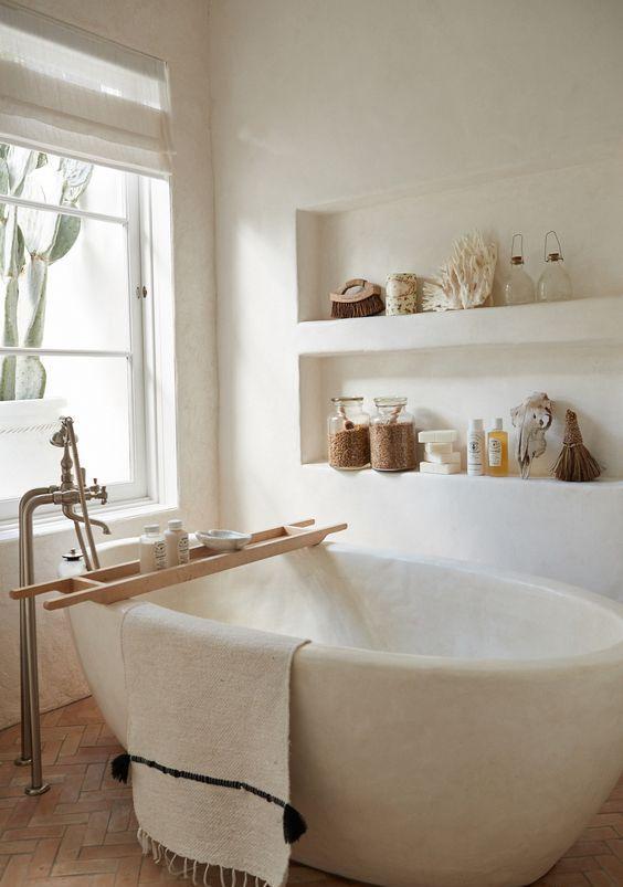 un bagno bianco rivestito totalmente di intonaco, con mensole incassate e con vasca in pietra bianca