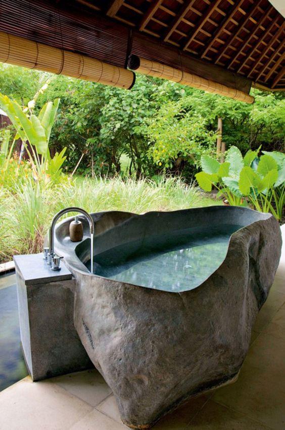 una vasca da bagno in pietra all'aperto con bordi irregolari ti manterrà fresco fuori durante le giornate calde