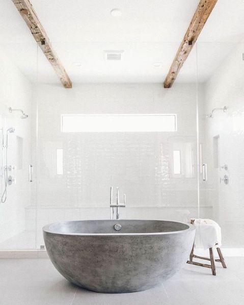 un bagno tutto bianco con vasca in pietra grigia, travi in legno che rendono l'ambiente più caldo e accattivante
