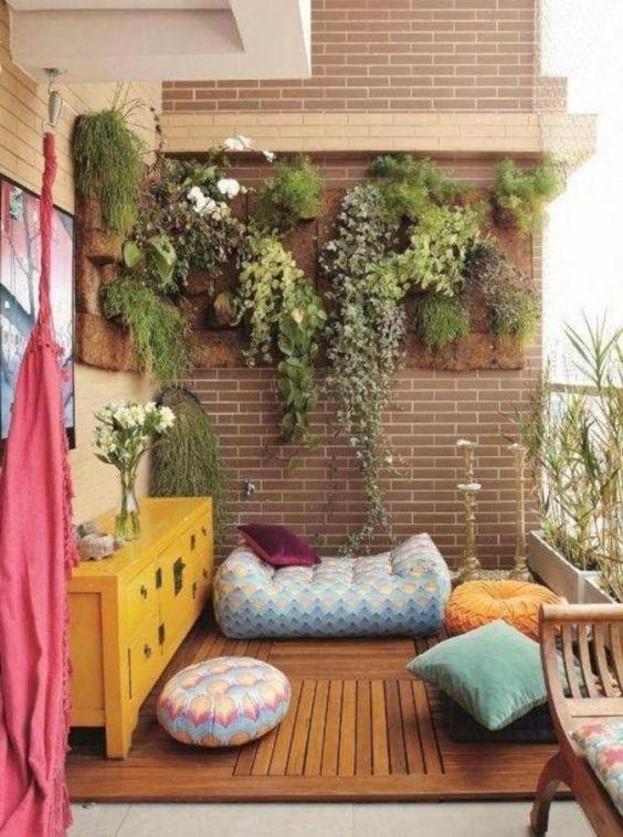 cuscini colorati e guanciali, una cassapanca luminosa, una coperta e un po 'di verde in vasi sul muro