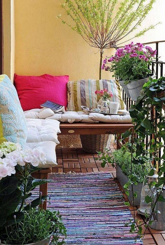 cuscini colorati e un tappeto boho, piante in vaso e fiori sono audaci e freschi per un balcone rustico