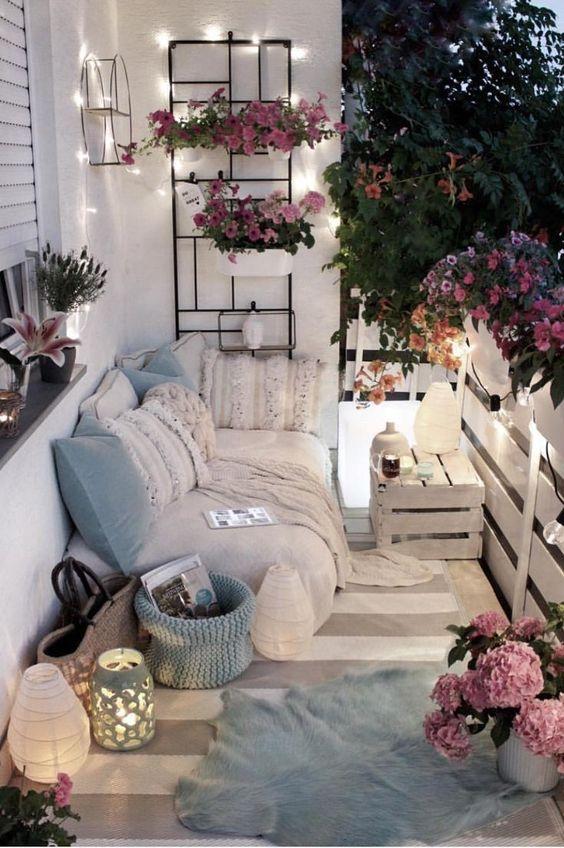 cuscini azzurri e un cesto, fiori rosa in vaso e alcune luci e lanterne renderanno il tuo balcone tenero e primaverile