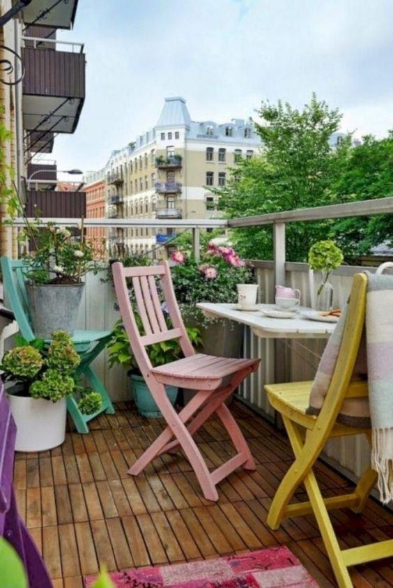 sedie pastello, un tappeto colorato, fiori in vaso e vegetazione per un comodo e chic balcone primaverile