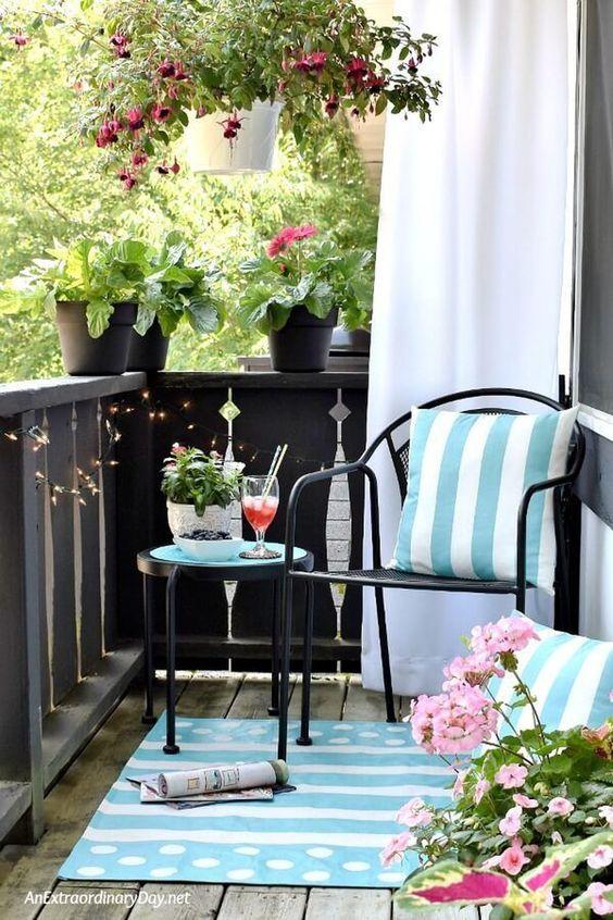 cuscini stampati azzurri e un tappeto e fiori rosa in vaso trasformano questo balcone in uno spazio luminoso e invitante