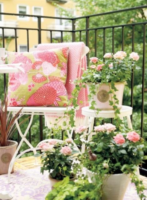 fiori in vaso e coperte e cuscini abbinati rendono il balcone fresco, colorato ed elastico